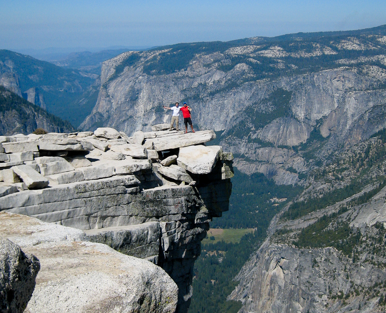 Two people standing on Half Dome's Visor with valley in background